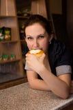 Νέα γυναίκα που τρώει το κέικ με το τυρί κρέμας στο φραγμό Στοκ φωτογραφίες με δικαίωμα ελεύθερης χρήσης