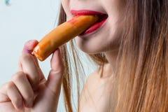 Νέα γυναίκα που τρώει το λουκάνικο ή το χοτ ντογκ το κορίτσι κάθεται στην κουζίνα και τρώει λαίμαργα το λουκάνικο στοκ εικόνες