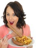 Νέα γυναίκα που τρώει το τεράστια λουκάνικο και τα τσιπ στοκ φωτογραφία με δικαίωμα ελεύθερης χρήσης