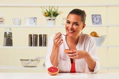 Νέα γυναίκα που τρώει το υγιές μεσημεριανό γεύμα διατροφής σταφυλιών φρούτων πρόχειρων φαγητών Στοκ Εικόνες