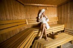 Νέα γυναίκα που τυλίγεται σε μια άσπρη χαλάρωση πετσετών στην ξύλινη σάουνα Στοκ Φωτογραφίες