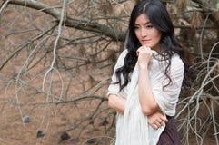 Νέα γυναίκα που τυλίγεται παραμονές στις άσπρες μαντίλι στο δάσος Στοκ Φωτογραφίες
