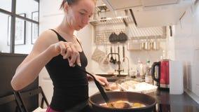 Νέα γυναίκα που υπερασπίζεται τη σόμπα στην κουζίνα και που προετοιμάζει το πρόγευμα για την οικογένεια, βίντεο τρόπου ζωής Καθημ απόθεμα βίντεο