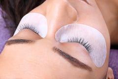 Νέα γυναίκα που υποβάλλεται eyelash στη διαδικασία επεκτάσεων, στοκ εικόνα με δικαίωμα ελεύθερης χρήσης