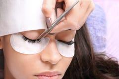 Νέα γυναίκα που υποβάλλεται eyelash στη διαδικασία επεκτάσεων, στοκ φωτογραφία με δικαίωμα ελεύθερης χρήσης