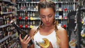 Νέα γυναίκα που φαίνεται συγκεχυμένη επιλέγοντας το κρασί στο κατάστημα απόθεμα βίντεο