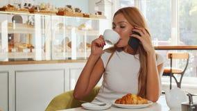 Νέα γυναίκα που φαίνεται συγκινημένη, μιλώντας στο τηλέφωνο ενώ έχοντας τον καφέ απόθεμα βίντεο