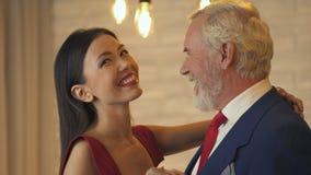 Νέα γυναίκα που φλερτάρει και που χορεύει με τον παλαιό εκατομμυριούχο κατά την ημερομηνία, υπηρεσία συνοδειών φιλμ μικρού μήκους