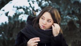 Νέα γυναίκα που φορά τα άσπρα ακουστικά υπαίθρια το χειμώνα Νέα ελκυστική γυναίκα στο μαύρο παλτό που φορά το άσπρο τράβηγμα-σκοι απόθεμα βίντεο