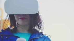 Νέα γυναίκα που φορά τα γυαλιά VR, την κάσκα, τα παίζοντας εικονικά παιχνίδια και τα βίντεο προσοχής υπαίθρια στα πλαίσια του α απόθεμα βίντεο
