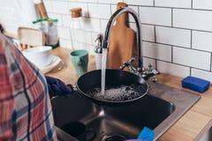 Νέα γυναίκα που φορά τα λαστιχένια γάντια που πλένουν το τηγανίζοντας τηγάνι στην κουζίνα Στοκ Εικόνες