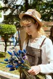 Νέα γυναίκα που φορά την εξάρτηση αγροτών και που κρατά την ανθοδέσμη wildflowers στοκ φωτογραφία με δικαίωμα ελεύθερης χρήσης