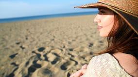 Νέα γυναίκα που φορά τη χαλάρωση καπέλων αχύρου στην παραλία φιλμ μικρού μήκους