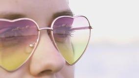Νέα γυναίκα που φορά τις σκιές κοιτάζοντας μακριά απόθεμα βίντεο