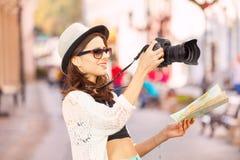 Νέα γυναίκα που φορά τους βλαστούς γυαλιών ηλίου με τη κάμερα Στοκ εικόνα με δικαίωμα ελεύθερης χρήσης