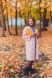 Νέα γυναίκα που φορά το καθιερώνον τη μόδα ρόδινο παλτό στο πάρκο φθινοπώρου εξέταση τη κάμερα δασική εποχή μονοπατιών πτώσης φθι στοκ εικόνα