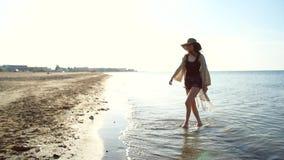Νέα γυναίκα που φορά το καπέλο αχύρου που απολαμβάνεται και που χορεύει θαλασσίως φιλμ μικρού μήκους