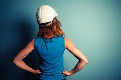 Νέα γυναίκα που φορά το σκληρό καπέλο Στοκ εικόνα με δικαίωμα ελεύθερης χρήσης