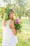 Νέα γυναίκα που φορά το στεφάνι των λουλουδιών και της ανθοδέσμης Στοκ εικόνα με δικαίωμα ελεύθερης χρήσης
