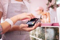 Νέα γυναίκα που φορά το συμπαθητικό άσπρο wristwatch που πληρώνει για τον καφέ της στοκ εικόνες με δικαίωμα ελεύθερης χρήσης