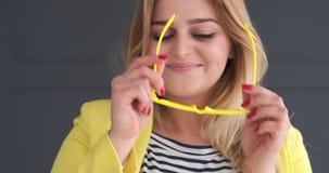 Νέα γυναίκα που φορά eyeglasses και που φυσά ένα φιλί φιλμ μικρού μήκους