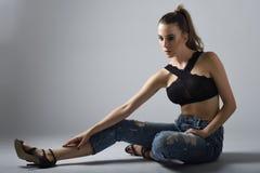 Νέα γυναίκα που φορούν το μαύρο στηθόδεσμο και τζιν παντελόνι που κάθεται στο πάτωμα S Στοκ Φωτογραφίες