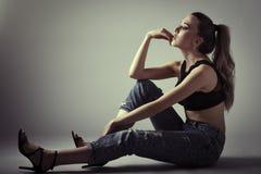 Νέα γυναίκα που φορούν το μαύρο στηθόδεσμο και τζιν παντελόνι που κάθεται στο πάτωμα S Στοκ Εικόνες