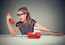 Νέα γυναίκα που φωνάζει στο κόκκινο τηλέφωνο Στοκ Εικόνες