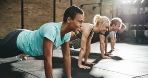 Νέα γυναίκα που χαμογελά κάνοντας pushups σε μια κατηγορία άσκησης στοκ εικόνα