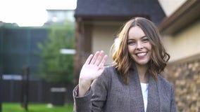 Νέα γυναίκα που χαμογελά και που κυματίζει το χέρι της εξετάζοντας τη κάμερα στην οδό απόθεμα βίντεο