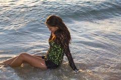 Νέα γυναίκα που χαμογελά καθμένος στον ωκεανό στοκ εικόνες