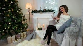 Νέα γυναίκα που χαλαρώνει και που διαβάζει το βιβλίο, καθμένος στον καναπέ, γυναίκα που φορά ένα θερμό πλεκτό πουλόβερ, Χριστούγε φιλμ μικρού μήκους