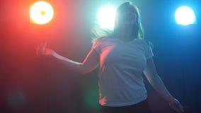 Νέα γυναίκα που χορεύει σε ένα φως χρώματος disco απόθεμα βίντεο
