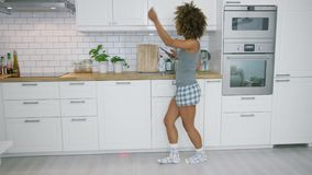 Νέα γυναίκα που χορεύει στην κουζίνα με το smartphone απόθεμα βίντεο