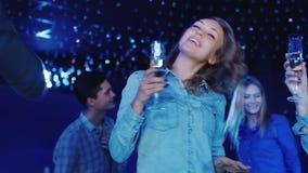 Νέα γυναίκα που χορεύει στο disco με ένα ποτήρι της σαμπάνιας Χόμπι και ελεύθερος χρόνος διασκέδασης απόθεμα βίντεο