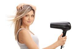 Νέα γυναίκα που χρησιμοποιεί ένα hairdryer Στοκ εικόνα με δικαίωμα ελεύθερης χρήσης