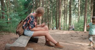 Νέα γυναίκα που χρησιμοποιεί ένα smartphone σε ένα δάσος Στοκ εικόνες με δικαίωμα ελεύθερης χρήσης