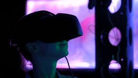 Νέα γυναίκα που χρησιμοποιεί την κάσκα εικονικής πραγματικότητας στη σκοτεινή διαλογική έκθεση απόθεμα βίντεο