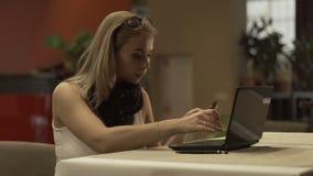 Νέα γυναίκα που χρησιμοποιεί την πλαστικά τραπεζική κάρτα και το lap-top για on-line να ψωνίσει σε Διαδίκτυο φιλμ μικρού μήκους