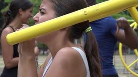Νέα γυναίκα που χρησιμοποιεί τη μηχανή άσκησης απόθεμα βίντεο