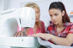 Νέα γυναίκα που χρησιμοποιεί τη ράβοντας μηχανή με το δάσκαλο Στοκ φωτογραφία με δικαίωμα ελεύθερης χρήσης