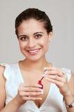 Νέα γυναίκα που χρησιμοποιεί τη στιλβωτική ουσία καρφιών Στοκ φωτογραφία με δικαίωμα ελεύθερης χρήσης