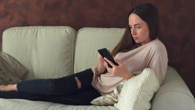 Νέα γυναίκα που χρησιμοποιεί τη συνεδρίαση smartphone στον καναπέ στο σπίτι απόθεμα βίντεο