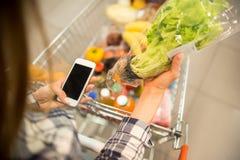 Νέα γυναίκα που χρησιμοποιεί τις αγορές App παντοπωλείων Στοκ εικόνα με δικαίωμα ελεύθερης χρήσης