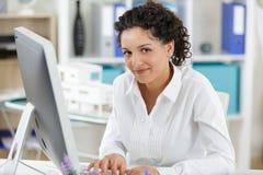 Νέα γυναίκα που χρησιμοποιεί τον υπολογιστή γραφείου στην αρχή στοκ εικόνες με δικαίωμα ελεύθερης χρήσης