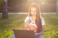 Νέα γυναίκα που χρησιμοποιεί τον υπολογιστή στις πράσινες χλόες στο πάρκο Εκμάθηση εκπαίδευσης ή ανεξάρτητη εργασία υπαίθρια ή χα Στοκ φωτογραφίες με δικαίωμα ελεύθερης χρήσης