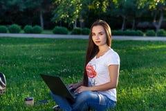 Νέα γυναίκα που χρησιμοποιεί τον υπολογιστή στις πράσινες χλόες στο πάρκο Εκμάθηση εκπαίδευσης ή ανεξάρτητη εργασία υπαίθρια ή χα Στοκ εικόνες με δικαίωμα ελεύθερης χρήσης