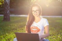Νέα γυναίκα που χρησιμοποιεί τον υπολογιστή στις πράσινες χλόες στο πάρκο Εκμάθηση εκπαίδευσης ή ανεξάρτητη εργασία υπαίθρια ή χα Στοκ Εικόνες