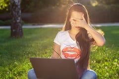 Νέα γυναίκα που χρησιμοποιεί τον υπολογιστή στις πράσινες χλόες στο πάρκο Εκμάθηση εκπαίδευσης ή ανεξάρτητη εργασία υπαίθρια ή χα Στοκ εικόνα με δικαίωμα ελεύθερης χρήσης