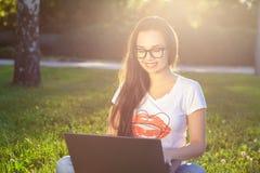 Νέα γυναίκα που χρησιμοποιεί τον υπολογιστή στις πράσινες χλόες στο πάρκο Εκμάθηση εκπαίδευσης ή ανεξάρτητη εργασία υπαίθρια ή χα Στοκ Φωτογραφία